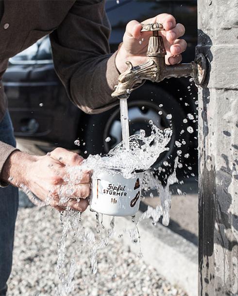 Roadtyping Emaille Becher am Brunnen